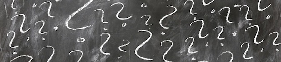 Question marks on black board