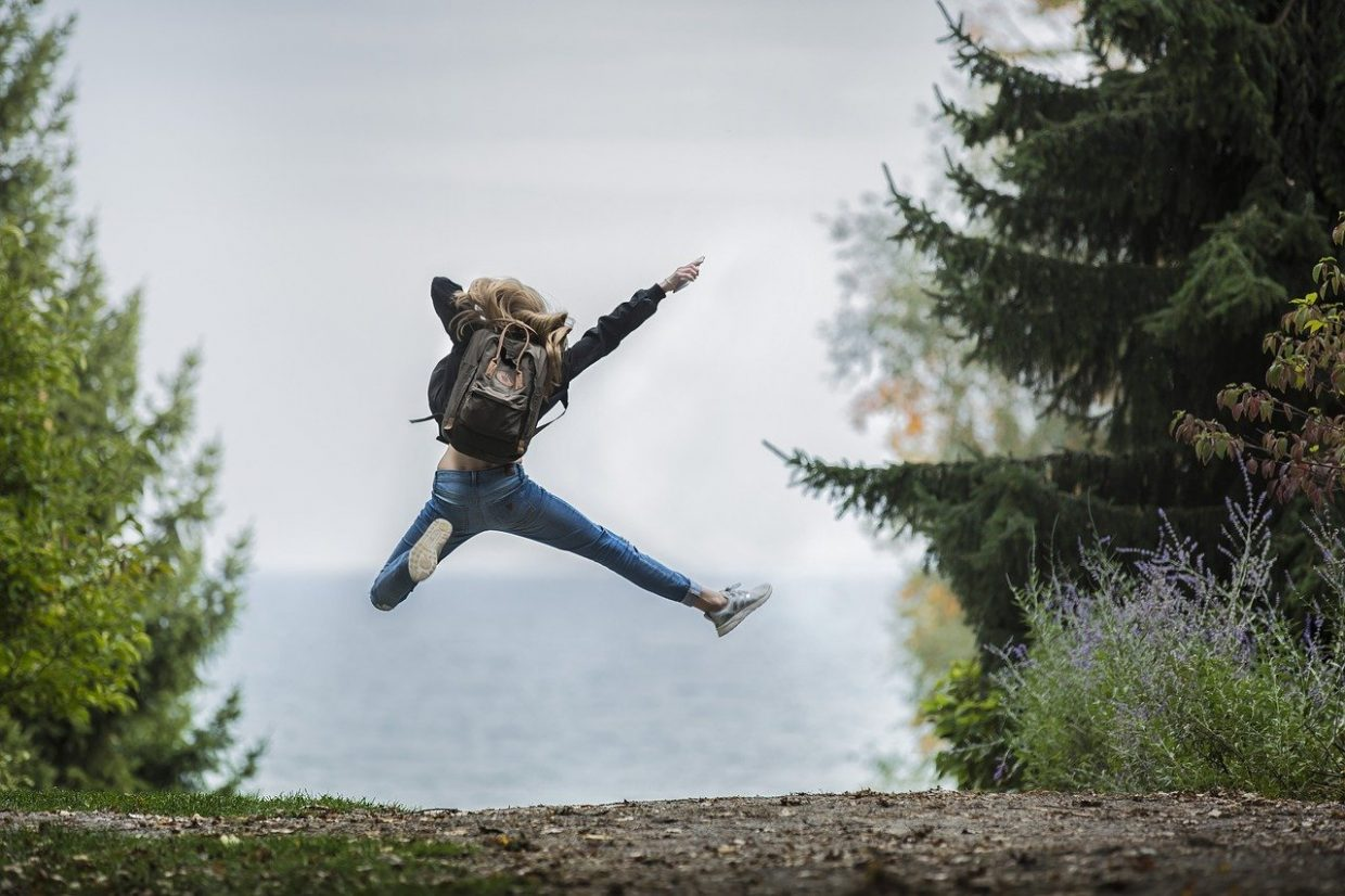 A woman traveler with backpack jumping in the wood