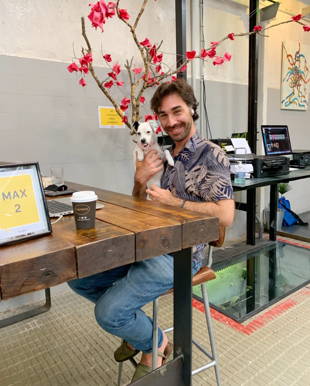 member of la vaca coworking Barcelona with a dog in his arms