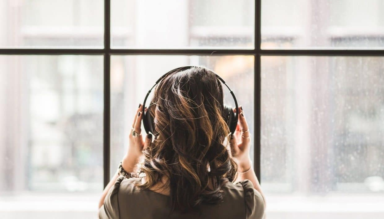 A woman standing at the window listening to music with headphones on a rainy day.