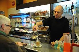 interior cafeteria palmer in poble sec with bartender serving a coffee